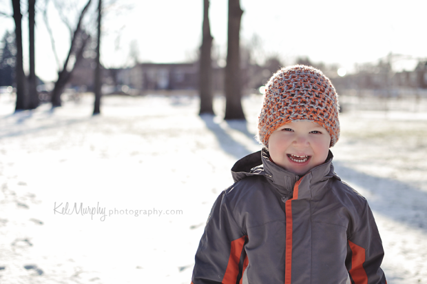 Kel Murphy Photography photo of son smiling with a background of snow and trees in Fox Chase, Philadelphia
