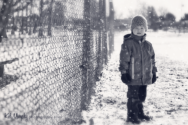 Kel Murphy Photography photo of son in the snow standing next to a fence in Burholme PA