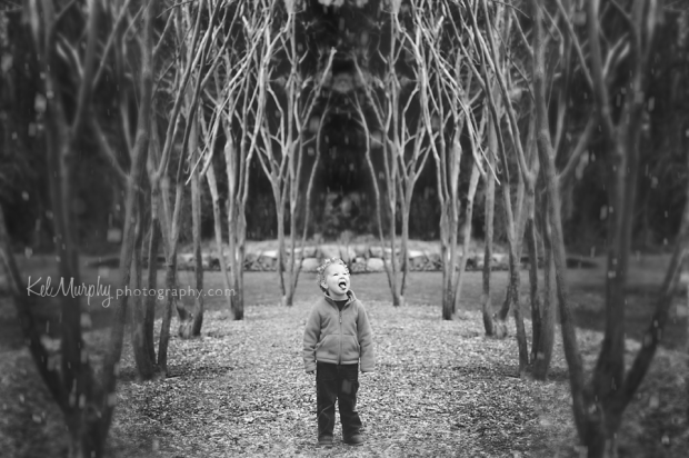 Kel Murphy Photography Day 37 of 365 BW son standing in the middle of winter trees catching snow with his tongue