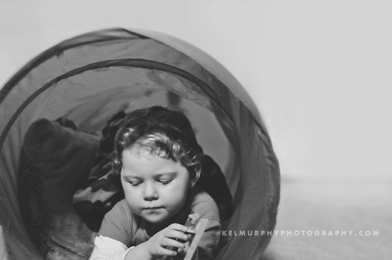 Kel Murphy Photography Day 43 of 365 son laying in tunnel reading books BW