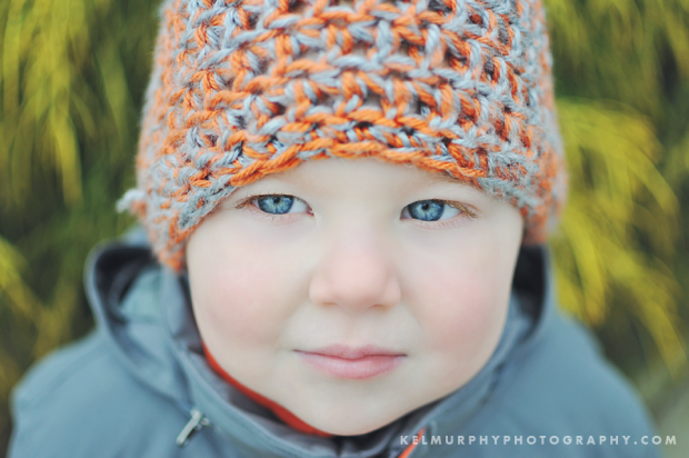 Kel Murphy Photography Day 47 of 365 son wearing knit hat standing in front of light green bush