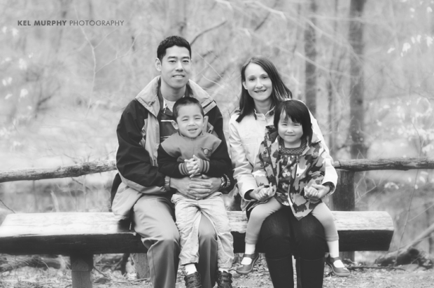 Family of four sitting on a bench smiling