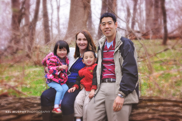 Family of four sitting on tree trunk in the fall