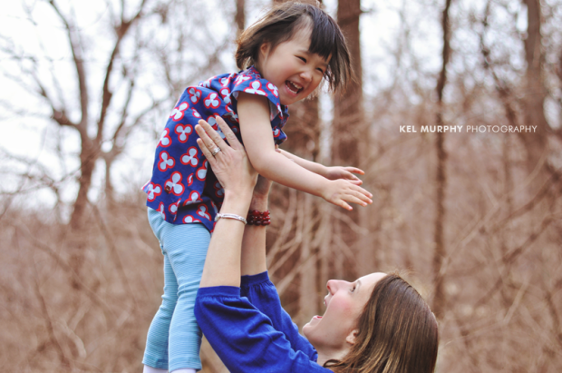 Mom throwing cute chinese daughter into the air