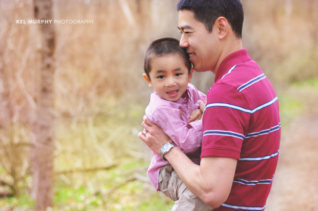 Chinese father holding son in his arms at the park