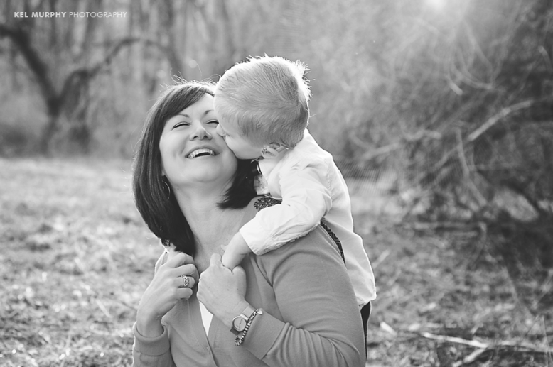 Young son has arms wrapped around Mom's neck and kissing her