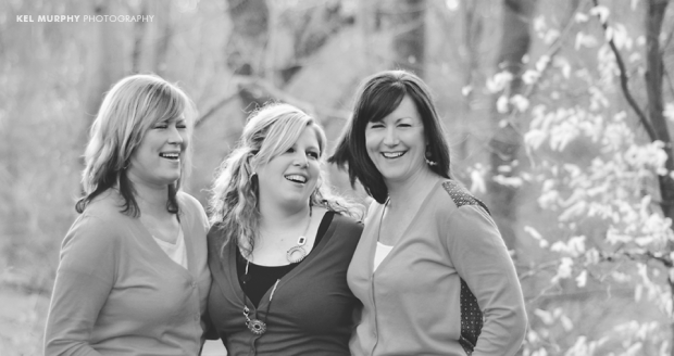 Three gorgeous women with arms around each other laughing