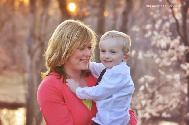 Aunt and young nephew holding each other during sunset