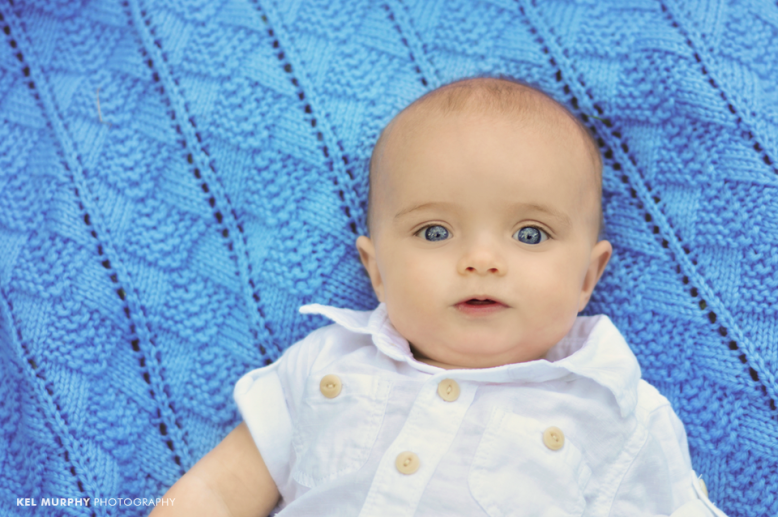 4 month old baby boy laying on blue blanket outside in the spring