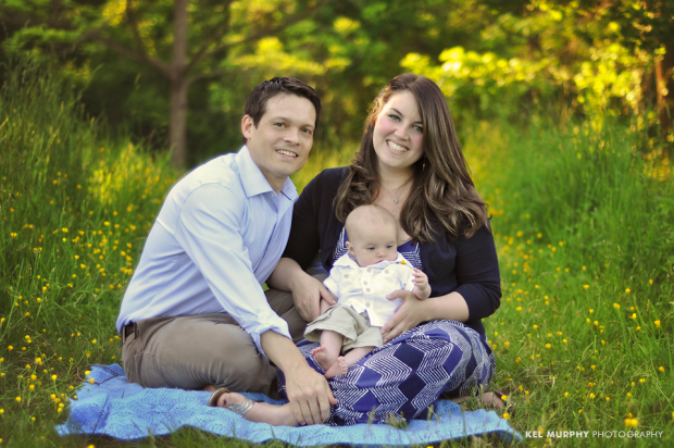 Family portrait of parents and 4 month old baby boy sitting outside surrounded by yellow spring flowers