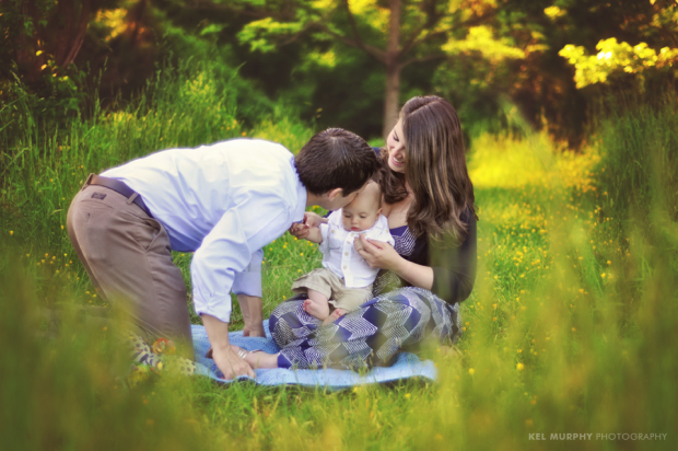 Lifestyle image of parents and 4 month old baby boy sitting outside surrounded by grass and yellow spring flowers