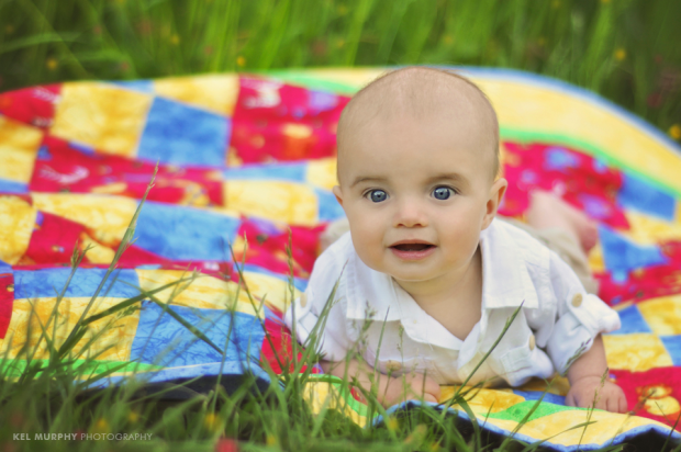 4 month old baby boy laying on stomach on colorful quilt surrounded by green grass and spring flowers