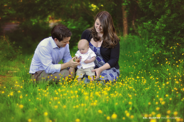 Lifestyle image of parents and 4 month old baby boy sitting outside surrounded by yellow spring flowers