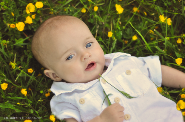 4 month old baby boy laying outside on green grass with yellow flowers around him