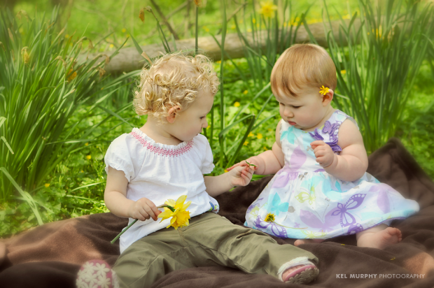 2 little girl cousins playing with flowers outside in the spring