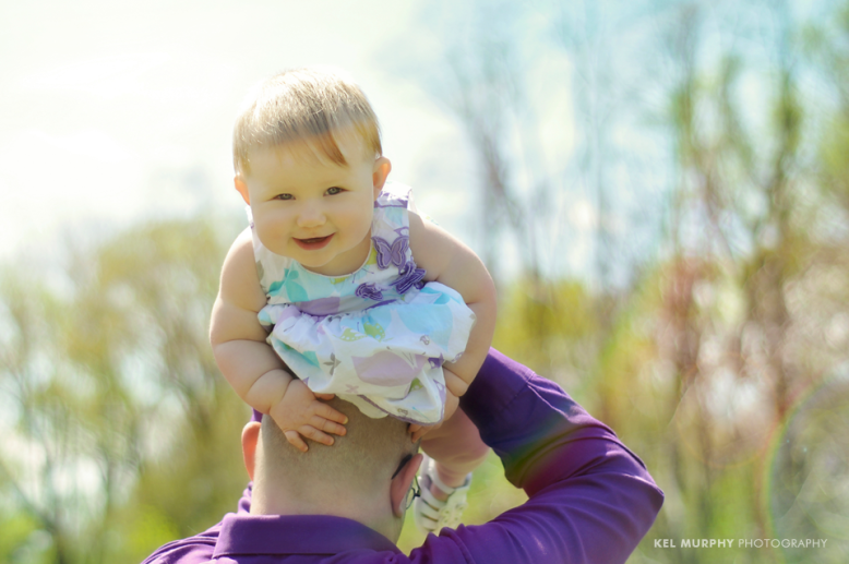 Father holding 6 month old baby girl over his head in the spring sunlight