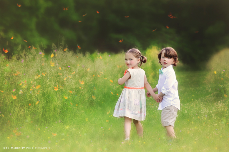 Twin brother and sister holding hands and walking down path in forest with butterflies