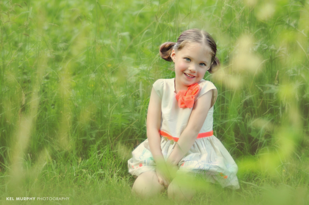Little girl wearing a dress sitting outside in the grass smiling in summer