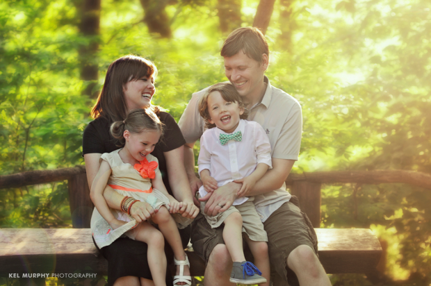 Family of four parents with boy and girl twins sitting on bench and laughing