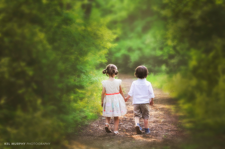 Twin brother and sister holding hands and walking down path in forest