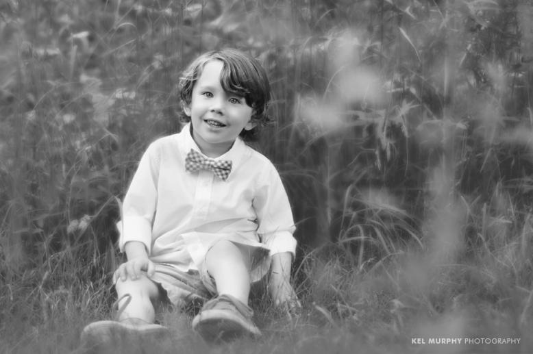 Little boy wearing bow tie outside in the summer