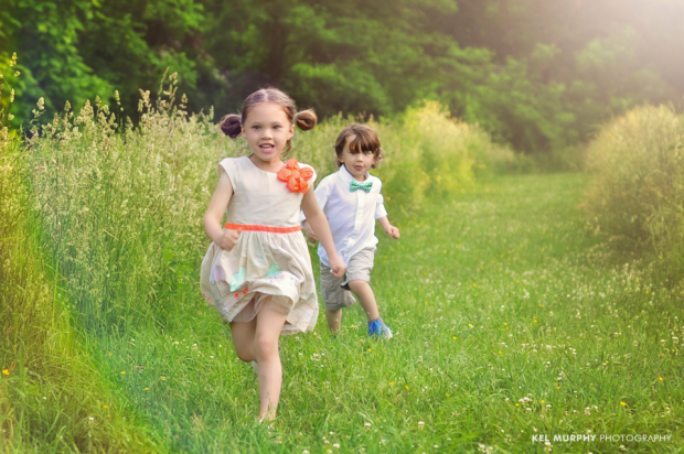 Twin brother and sister running in field in the summer