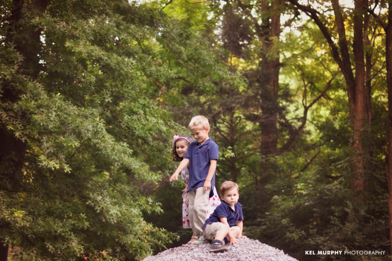 Three children playing on rock pile in forest