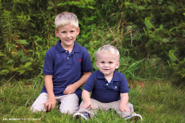 Young blonde brothers sitting outside on grass with matching blue shirts