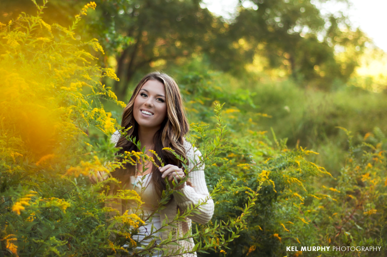 Pretty high school senior girl smiling and standing in field of goldenrod plant weeds