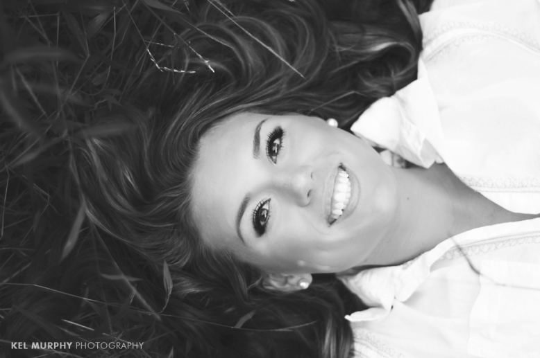 Pretty high school senior girl laying in grass with long hair around her face
