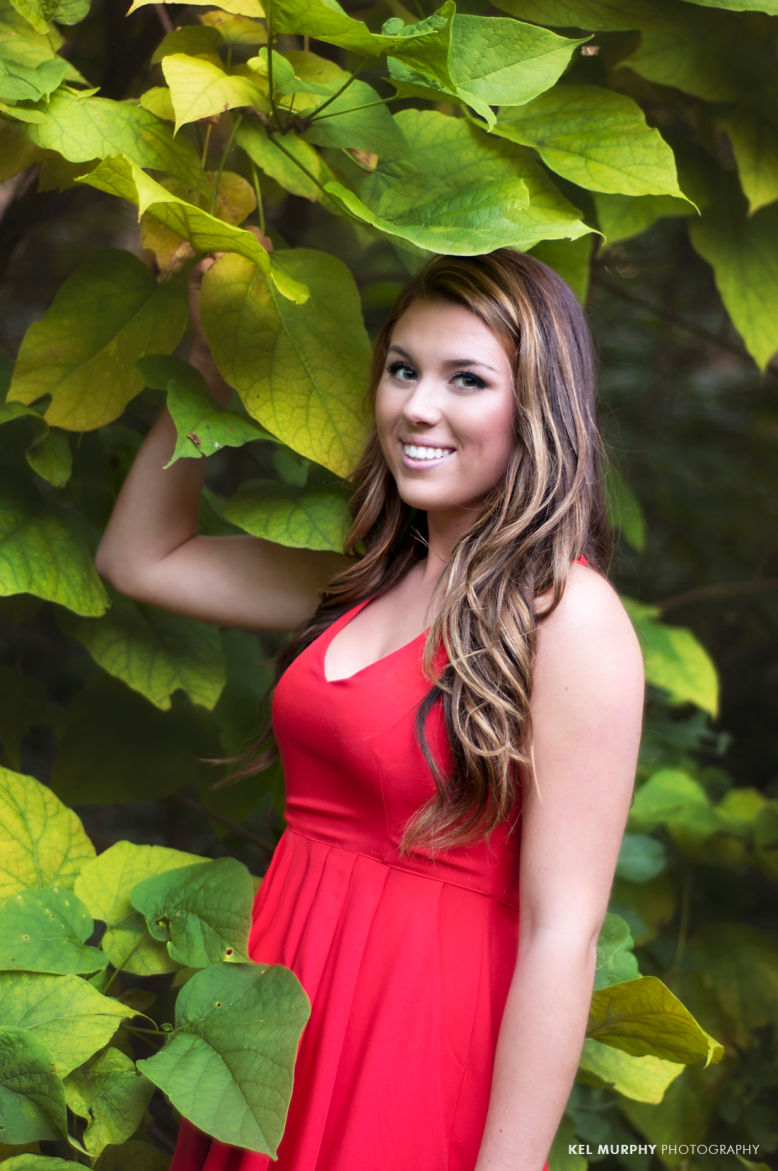 Pretty high school senior girl in red dress standing in front of big green leaves