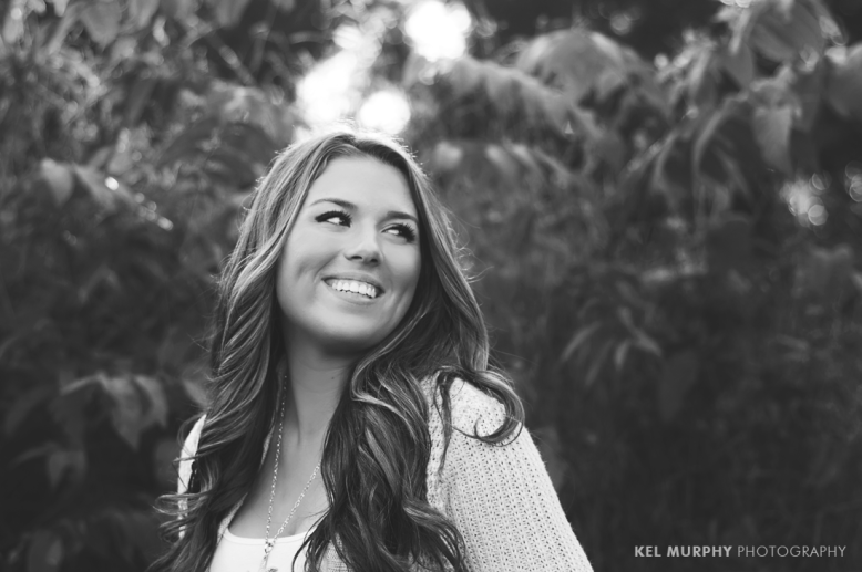 Pretty high school senior girl smiling laughing and looking over shoulder