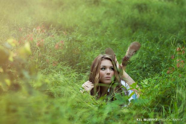 High school senior photography session with teen girl laying in grass with feet up