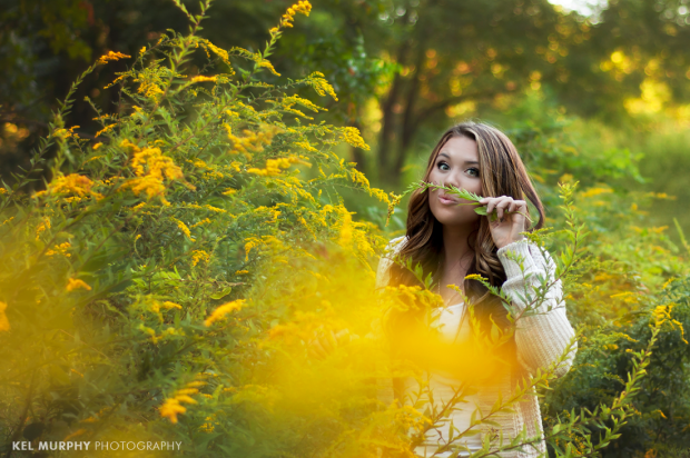 Pretty high school senior girl using goldenrod yellow plant to make a mustache
