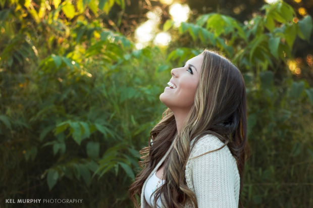 Pretty high school senior girl laughing outside showing profile