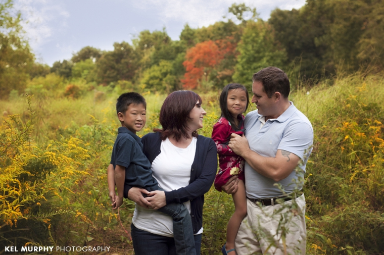Gorgeous family of four outside in the fall with yellow goldenrods lifestyle