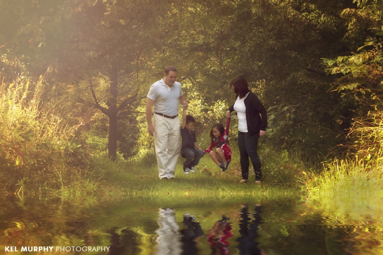 family of four parents swinging children near pond refection