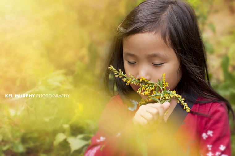 Little girl smelling goldenrod weed plant outside in the fall