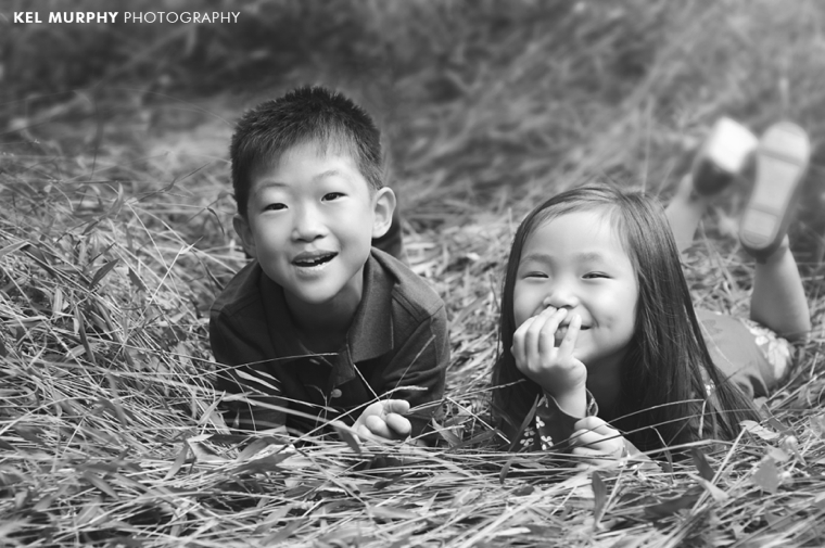 Young brother and sister laying down on stomach outside laughing
