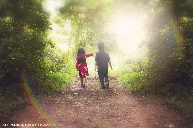 Brother and sister walking down pathway with rainbow sunflare