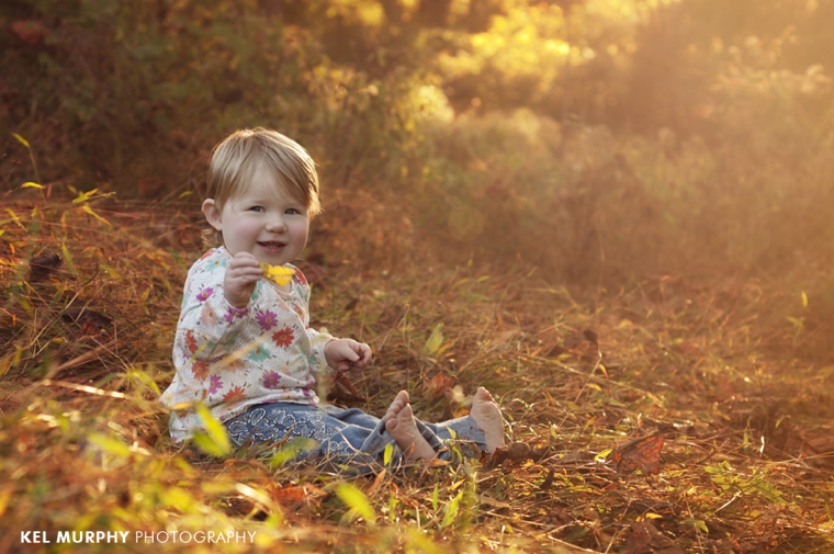 One and a half year old toddler girl sitting outside in the fall leaves