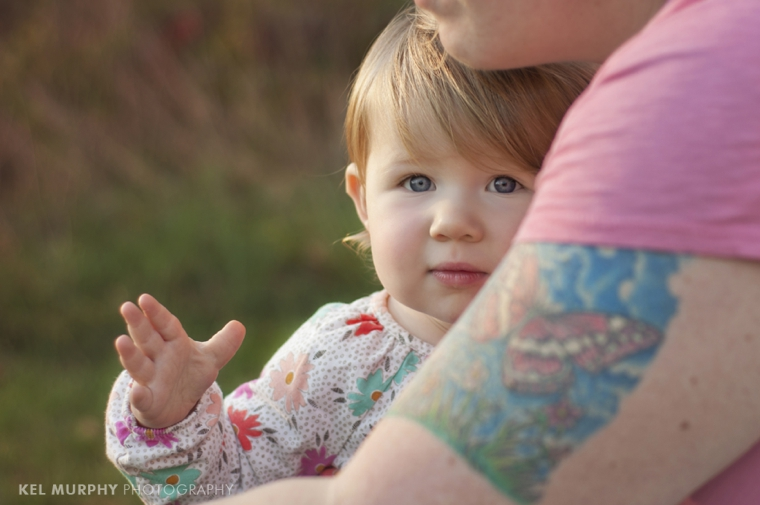 18 month old toddler girl standing outside in the fall, mom's butterfly tattoo is shown