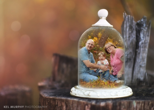 Family of three outside in the fall pregnant mommy in snow globe for christmas holiday cards
