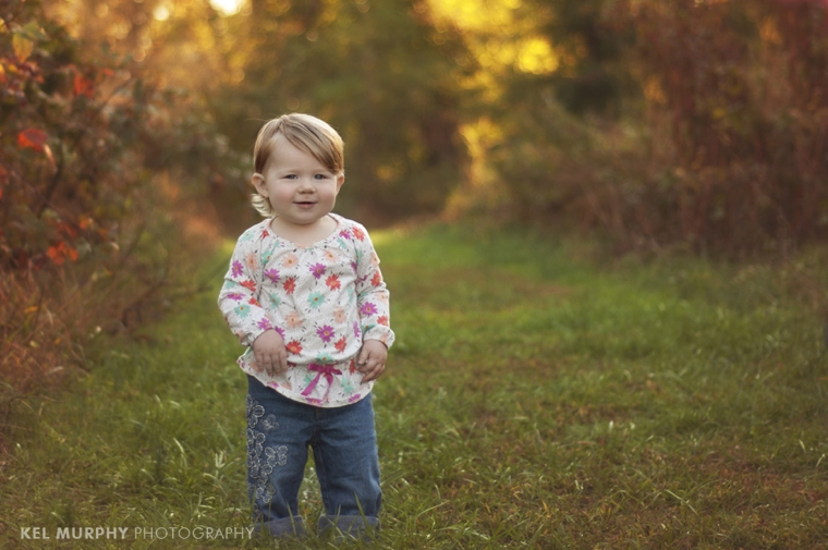 18 month old toddler girl standing outside in the fall, one and a half year old