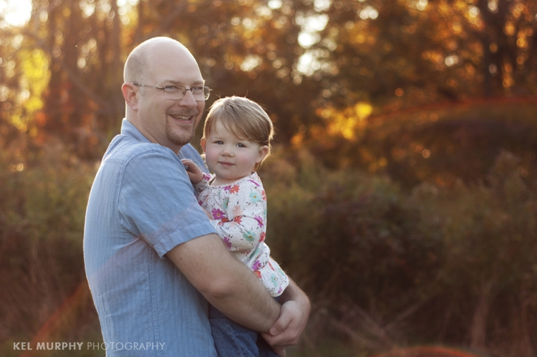 Daddy holding 18 month old toddler girl outside in the fall