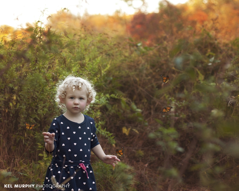 Two year old little girl with curly blonde hair outside in the fall with butterflies