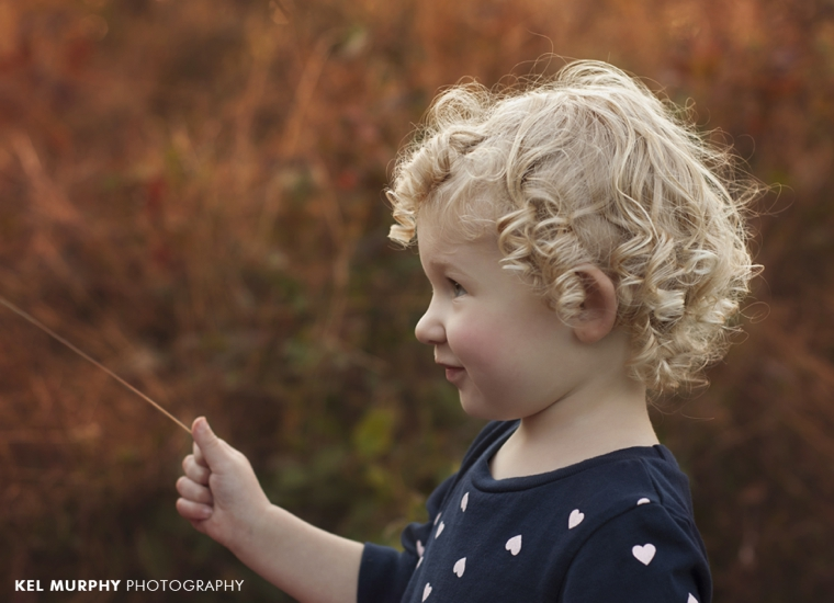Two year old little girl with curly blonde ringlets outside in the fall profile shot