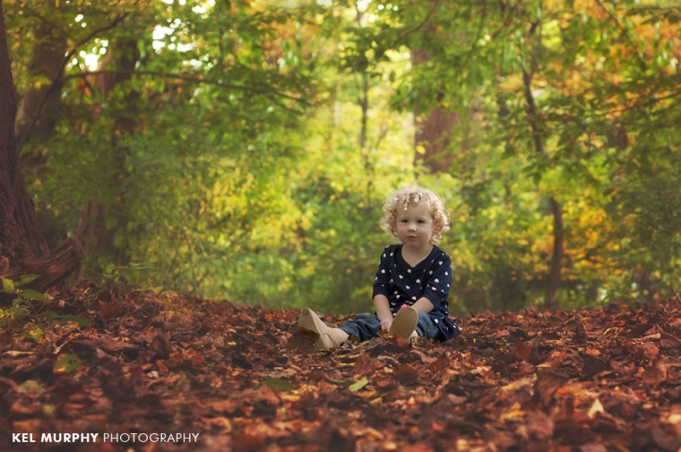 Two year old little girl with curly blonde hair sitting outside in the fall leaves