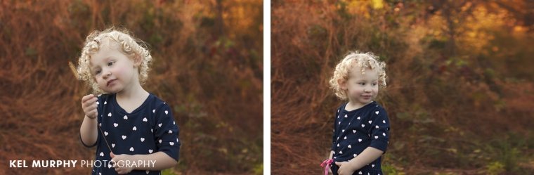 Two year old little girl with curly blonde hair outside in the fall