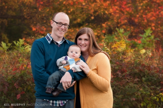 Kel Murphy Photography holiday mini sessions philadelphia abington montgomery county, family of three outside in the fall with pretty colored leaves in the background.